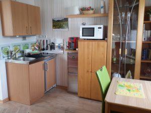 Spüle, Kühlschrank,Herd und Mikrowelle, sowie Esstisch